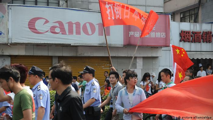 People in an anti-Japan protest pass by a closed shop of Canon products in Hangzhou in east China's Zhejiang province Sunday Sept. 16, 2012. Japan has urged China to ensure the safety of Japanese citizens and businesses in China after violence aiming at Japanese businesses and products are reported in the protests on Saturday. Photo via Newscom picture alliance