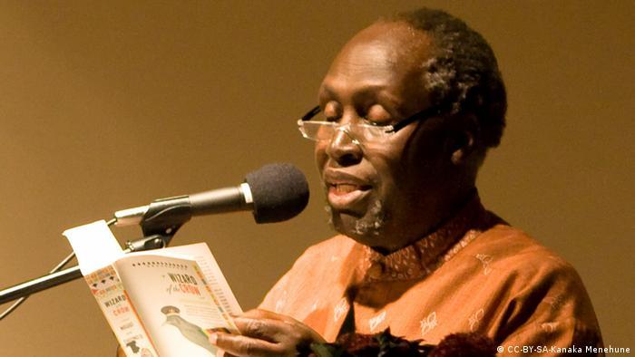 Kenyan author Ngugi wa Thiong'o reading a book using a microphone.