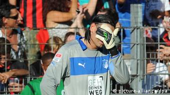 Tim Wiese with his head in his goalkeeping glove in a game against Freiburg