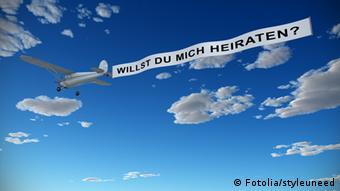 Ein Flugzeug in der Luft, das ein Banner mit der Aufschrift Willst du mich heiraten hinter sich herzieht