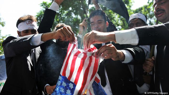 Pakistani lawyers burn a US flag as they attempt to reach the US embassy in the diplomatic enclave. Photo: AAMIR QURESHI/AFP/GettyImages)