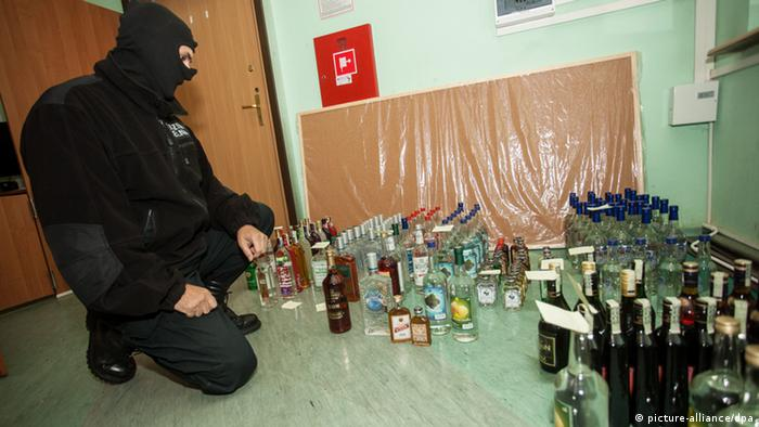 A masked customs office kneels down beside some 200 bottles of conviscated illegal alcohol (photo: EPA/MICHAL WALCZAK POLAND OUT)