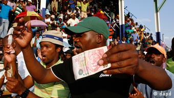 Miners sing and dance whilst holding South African bank notes in Lonmin Platinum Mine near Rustenburg, South Africa. Photo:Themba Hadebe/AP/dapd)
