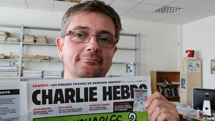Publishing director of the satyric weekly Charlie Hebdo, Charb, displays the front page of the newspaper as he poses for photographers in Paris, Wednesday, Sept. 19, 2012. Police took up positions outside the Paris offices of the satirical French weekly that published crude caricatures of the Prophet Muhammad on Wednesday that ridicule the film and the furor surrounding it. The provocative weekly, Charlie Hebdo, was firebombed last year after it released a special edition that portrayed the Prophet Muhammad as a guest editor and took aim at radical Islam. (Foto:MIchel Euler/AP/dapd)