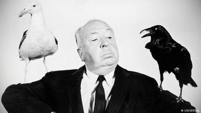 Werbefoto zu Alfred Hitchcocks Film 'Die Vögel': Der Regisseur trägt eine Möwe und einen Raben auf seinen Armen. (Foto: UNIVERSAL)