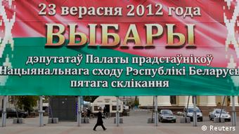 A man walks under a huge parliamentary election banner in Minsk September 17, 2012. Belarus's two main opposition parties said they would boycott a parliamentary election next Sunday, denouncing it as a fake exercise and are calling on people to go fishing or visit your parents instead. The banner reads: September 23, 2012. Parliamentary election of deputies to the House of Representatives of the National Assembly of Belarus. REUTERS/Vasily Fedosenko (BELARUS - Tags: POLITICS ELECTIONS)