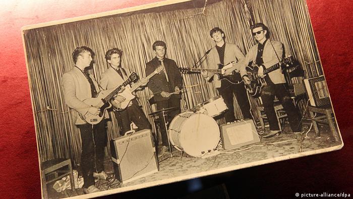 Cinco jovens de pé, de paletó, cada um com um instrumento musical