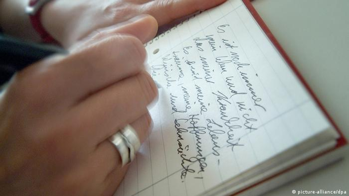 a hand writing in pen (picture-alliance/dpa)