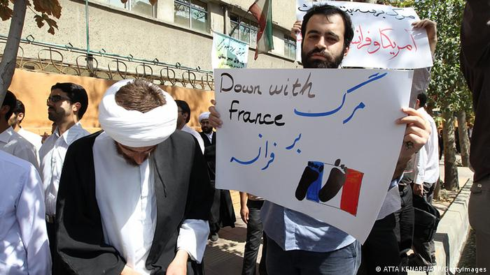 Iranian men hold slogans during a demonstration against the publication by a French satirical weekly of a cartoon of a naked Prophet Mohammed, on September 20, 2012 outside France's embassy in Tehran. Photo: ATTA KENARE/AFP/GettyImages