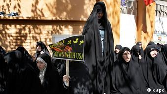 Iranian women pray as one holds an anti-U.S. placard in front of the French Embassy in Tehran, Iran, Thursday, Sept. 20, 2012, during a protest the publication of caricatures of Islam's Prophet Muhammad by a French satirical weekly. Dozens of Iranian students and clerics gathered outside the embassy and chanted Death to France and Down with the U.S. and burned the representation of the U.S. and Israeli flags Thursday. Photo: Vahid Salemi/AP/dapd