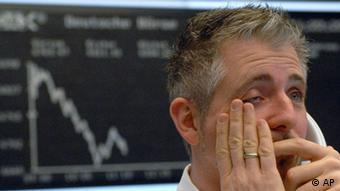 Ein verzweifelter Aktien-Broker steht vor einer Darstellung der DAX-Kurve
