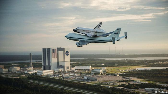 The space shuttle Endeavour, atop NASA's Shuttle Carrier Aircraft, flies over the Kennedy Space Center in Cape Canaveral, Florida in this September 19, 2012 NASA handout photo. The SCA, a modified 747 jetliner is flying Endeavour to Los Angeles where it will be placed on public display at the California Science Center.