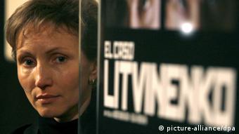 A woman next to a poster photo: EPA/JUAN CARLOS HIDALGO
