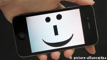 ILLUSTRATION - Auf einem Mobiltelefon ist am Mittwoch (12.09.2012) in Stuttgart ein Smiley Symbol zu sehen. Am Mittwoch 19.09.2012 wird der auf der Seite liegende Smiley 30 Jahre alt. Längst ist die auf jeder gängigen Tastatur zu erzeugende Zeichenfolge rund um den Online-Smiley Bestandteil der Schreibkultur wie etwa in E-Mails, Chats oder der Kurzmitteilung SMS. Foto: Franziska Kraufmann dpa/lsw (Zu lsw Korr: Glückwunsch :-) Seit 30 Jahren geistert das Grinsegesicht durchs Netz vom 13.09.2012) +++(c) dpa - Bildfunk+++
