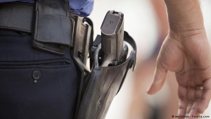 Рука полицейского крупным планом возле кобуры с пистолетом
