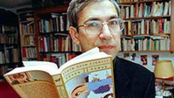Turkish author Orhan Pamuk holding up a book with book shelves in background