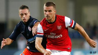 Montpellier's French midfielder Jamel Saihi, left, challenges for the ball with Arsenal's German forward Lukas Podolski, during the Champions League Group B soccer match between Montpellier and Arsenal, at the La Mosson stadium, in Montpellier, southern France, Tuesday, Sept.18, 2012. (AP Photo/Claude Paris)