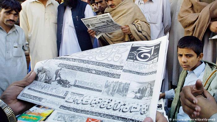 Afghan refugees stand reading newspaper. dpa