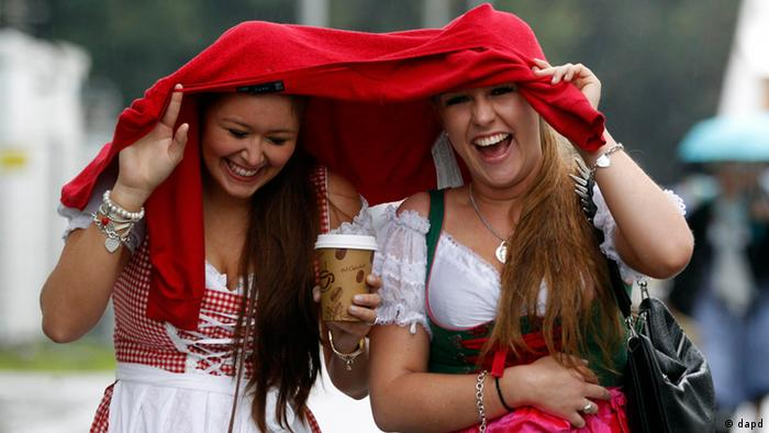 Two women react, as they arrive for the opening of the famous Bavarian Oktoberfest beer festival as rain falls, in Munich, southern Germany, Saturday, Sept. 22, 2012. (Foto: AP)