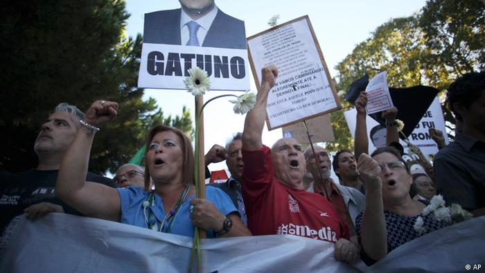 People protest outside the presidential palace in the Lisbon suburb of Belem during a meeting of the State Council, a presidential advisory body, Friday, Sept. 21, 2012. Portugal's President Anibal Cavaco Silva called the state council members to discuss the current economic and political situation in the country. The banner with the photo of the Portugal's Prime Minister Pedro Passos Coelho reads in Portuguese: Thief. (Foto:Francisco Seco/AP/dapd).