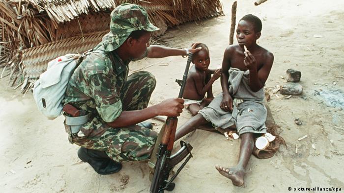 Cena no campo de refugiados internos de Dondo, centro de Moçambique, em 1988: um soldado aproxima-se de uma mulher que fugiu com o seu filho dos ataques da RENAMO