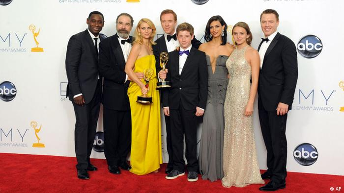 Actors, from left, David Harewood, Mandy Patinkin, Claire Danes, Damian Lewis, Jackson Pace, Morena Baccarin, Morgan Saylor and Diego Klattenhoff, of the Outstanding Drama Series award-winning series Homeland, pose backstage at the 64th Primetime Emmy Awards at the Nokia Theatre on Sunday, Sept. 23, 2012, in Los Angeles. (Photo by Jordan Strauss/Invision/AP)