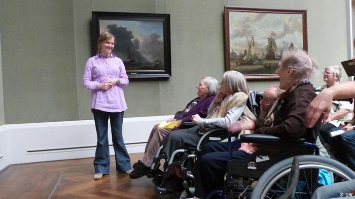 An group of dementia patients in wheelchairs watch a tour guide introduce a work of art.