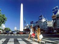 Zwei Frauen mit Einkaufstaschen überqueren vor dem Obelisken die Avenida 9 de Julio in Buenos Aires. Undatiert.