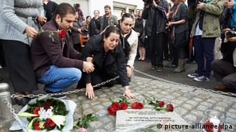 Mehmet Kubasik's widow (c) kneeling in front of a commemorative plate on the street not far from the original crime scene Copyright: Bernd Thissen/dpa