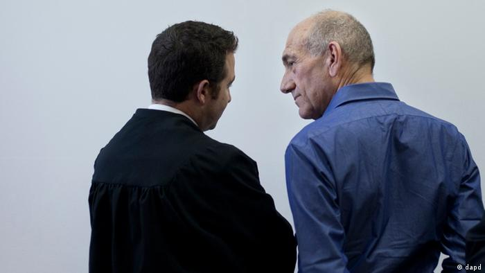 Former Israeli Prime Minister Ehud Olmert, right, speaks with his attorney as he attends the sentence hearing in a corruption case, at Jerusalem's District Court, Monday, Sept. 24, 2012. Olmert cleared a major hurdle toward a possible return to politics on Monday, receiving an unexpectedly light sentence for his role in a corruption case that forced him from office. (AP Photo/Sebastian Scheiner, Pool)