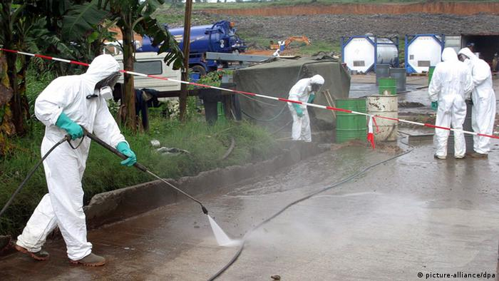Workers in white biohazard suits spray the ground in an attemp to remove toxic chemicals. EPA/LEGNAN KOULA