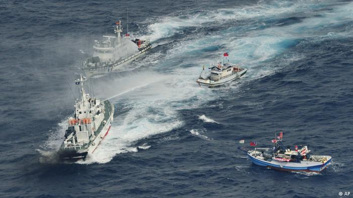 A Japan Coast Guard's patrol boat, left bottom, discharges water against Taiwanese fishing boats near disputed islands called Senkaku in Japan and Diaoyu in China, in the East China Sea, Tuesday, Sept. 25, 2012. On Tuesday morning, about 50 Taiwanese fishing boats accompanied by 10 Taiwanese surveillance ships came within almost 20 kilometers (about 12 miles) of the disputed islands - within what Japan considers to be its territorial waters, said Yasuhiko Oku, an official with the Japanese coast guard. (Foto:Kyodo News/AP/dapd) JAPAN OUT, MANDATORY CREDIT, NO LICENSING IN CHINA, FRANCE, HONG KONG, JAPAN AND SOUTH KOREA