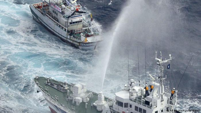 A Japan Coast Guard patrol boat sprays water against a Taiwanese fishing boat, top, near disputed islands, called Senkaku in Japan and Diaoyu in China, in the East China Sea, Tuesday, Sept. 25, 2012. Japanese coast guard ships fired water cannon to push back Taiwanese vessels Tuesday in the latest confrontation over a group of the tiny islands, as the main contenders, China and Japan, opened talks in a diplomatic effort to tamp down tensions. (AP Photo/Kyodo News) JAPAN OUT, MANDATORY CREDIT, NO LICENSING IN CHINA, FRANCE, HONG KONG, JAPAN AND SOUTH KOREA