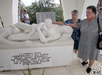 ** FILE ** Lilia Pardini, right, and her sister Licia touch a sculpture depicting their mother and sister who were killed along with more than 500 others in 1944 by Nazi SS troops, at the 60th anniversary commemoration ceremony of the slaughter in Sant'Anna di Stazzema, Italy, in this Thursday, Aug. 12, 2004 file photo. Italian judges Wednesday, June 22, 2005 convicted 10 former members of the Nazi SS accused of taking part in the massacre, and sentenced them in absentia to life in prison, a defense lawyer said. (AP Photo/Fabio Muzzi)