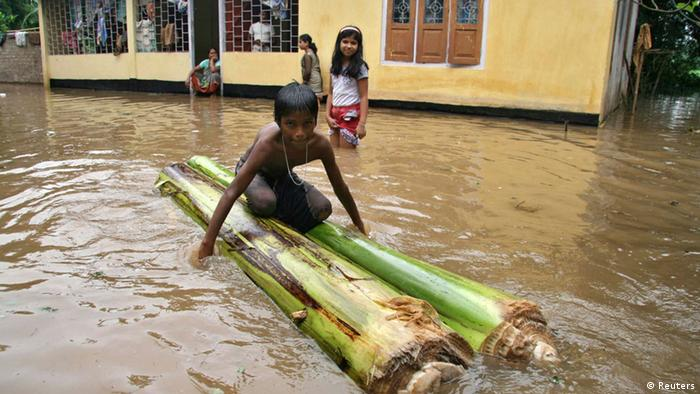 A boy sits on a raft made from banana trees outside his flooded house on the outskirts of Guwahati in the northeastern Indian state of Assam September 25, 2012. Floods and landslides caused by relentless rain in northeast India have killed at least 33 people and displaced more than a million over the past week, officials said on Monday. REUTERS/Utpal Baruah (INDIA - Tags: DISASTER ENVIRONMENT)