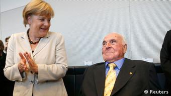 German Chancellor Angela Merkel applauds as former German chancellor Helmut Kohl (R) arrives for a Christian Democratic Union (CDU) and Christian Social Union (CSU) party faction meeting in the Reichstag building in Berlin, September 25, 2012. REUTERS/Fabrizio Bensch (GERMANY - Tags: POLITICS)