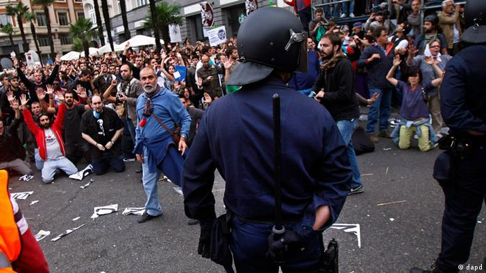 Protestors shout slogans as a riot policeman hides his nightstick during the demonstration at the parliament against austerity measures announced by the Spanish government in Madrid, Spain, Tuesday, Sept. 25, 2012. Spain's Parliament has taken on the appearance of a heavily guarded fortress with dozens of police blocking access from every possible angle, hours ahead of a protest against the conservative government's handling of the economic crisis. The demonstration, organized behind the slogan 'Occupy Congress,' is expected to draw thousands of people. It is due to start around 1730 GMT Tuesday. Madrid authorities said some 1,300 police would be deployed. The protestors call for Parliament to be dissolved and fresh elections held, claiming the government's austerity measures show the ruling Popular Party misled voters to get elected last November. (Foto:Andres Kudacki/AP/dapd)