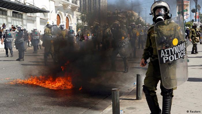 A molotov cocktail explodes beside riot police officers near Syntagma square during a 24-hour labour strike in Athens September 26, 2012. Flights and trains were suspended, shops pulled down their shutters and hospitals worked on emergency staff on Wednesday in Greece's first big anti-austerity strike since a coalition government took power in June. REUTERS/Yannis Behrakis (GREECE - Tags: BUSINESS CIVIL UNREST POLITICS)