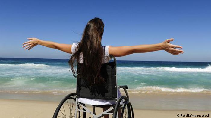 Женщина в инвалидной коляске на фоне моря