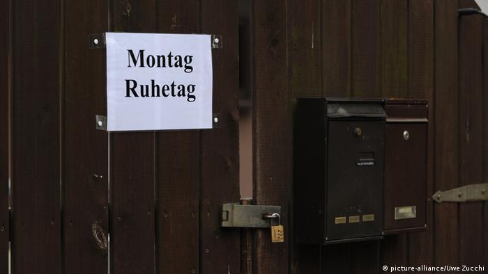 An einem Holztor hängt ein Schild: Montag Ruhetag
