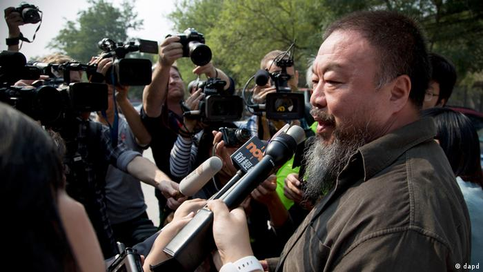 Chinese Activist artist Ai Weiwei, right, speaks to the journalists after attending his appeal case at the Beijing No. 2 People's Intermediate Court in Beijing Thursday, Sept. 27, 2012. Chinese authorities on Thursday rejected Ai's second appeal of a $2.4 million tax fine, meaning his design company will have to pay the penalty. (AP Photo/Andy Wong)