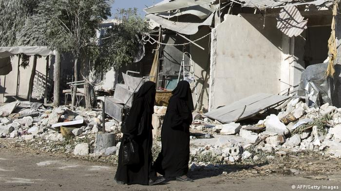 women walk past the rubble of a building in Aleppo, Syria