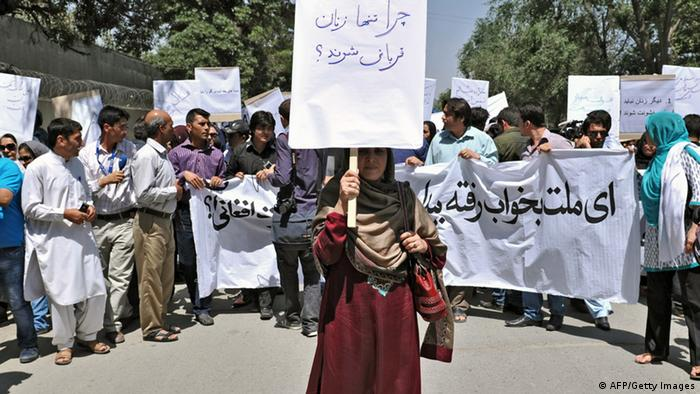 An Afghan woman, holding a placard which reads 'why just women are victims?', marches during a protest against the recent public execution of a young woman for alleged adultery, in Kabul Photo: MASSOUD HOSSAINI/AFP/GettyImages