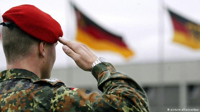 Ein Soldat salutiert vor der deutschen Fahne. (Foto: dpa)