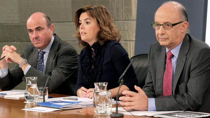 (L-R) Spain's Minister of Economy and Competitiveness Luis de Guindos, Spain's First deputy prime minister and government spokeswoman Soraya Saenz de Santamaria, and Spain's Minister of Treasury Cristobal Montoro hold a press conference to present a budget for 2013 at the Moncloa Palace in Madrid, Spain, 27 September 2012. The Spanish government approved a tough austerity budget for 2013 in its struggle to ward off an international bailout, defying new protests against its spending cuts. The government did not immediately put figures on the budget cuts, which had earlier been estimated at a total of 40 billion euros (51 billion US dollars).