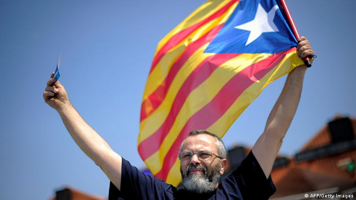 A man holds a catalan independentist flag 'la senyera' during a potest of the No Vull Pagar (I don't want to pay) movement during a demostration in Mollet's toll on July 29, 2012 in Mollet del Valles near Barcelona. Followers of the pressure group No Vull Pagar (I don't want to pay) who refuse to pay highway tolls, demonstrated against the toll company Abertis, owned by La Caixa. AFP PHOTO/JOSEP LAGO (Photo credit should read JOSEP LAGO/AFP/GettyImages)