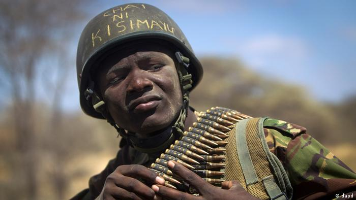 In this Tuesday, Feb. 21, 2012 file photo, Kenyan army soldier Nicholas Munyanya, wearing a helmet on which is written in Kiswahili Tea in Kismayo, referring to a key strategic Somali town then under the control of al-Shabab, checks his amunition.