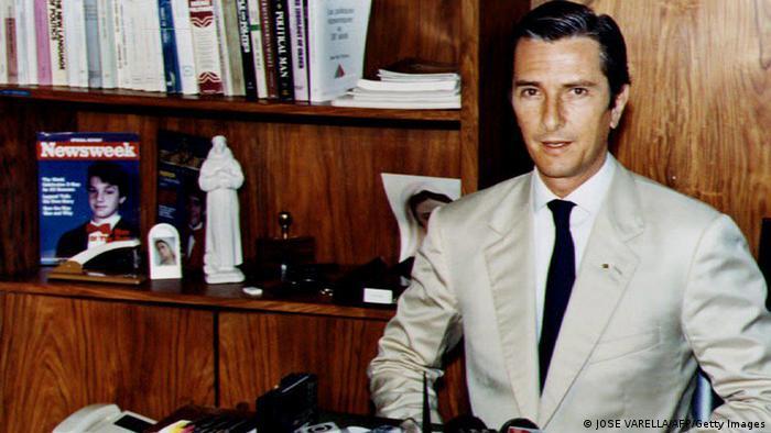 Fernando Collor de Mello sentado junto a uma estante