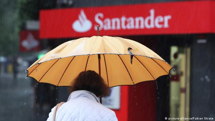 Spanish woman passing by a Santander office and holding an umbrella