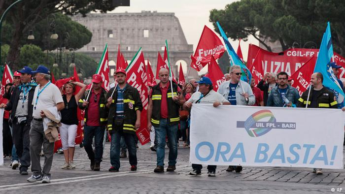 Public sector workers walk along Via dei Fori Imperiali, which leads to the ancient Colosseum, seen in background, holding flags of labor unions and a placard reading Now Stop! as they protest against the Italian government's spending cuts, in Rome, Friday Sept. 28, 2012.